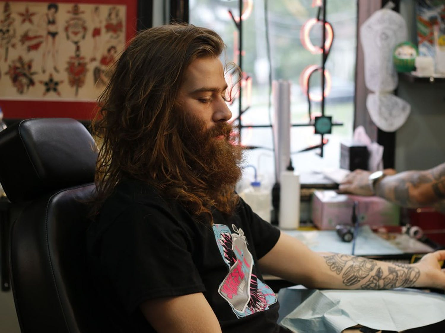 Mike Wheeler shades Hayden Fitzgerald's tattoo at Glenn's Tattoo Service on Monday in Carrboro.