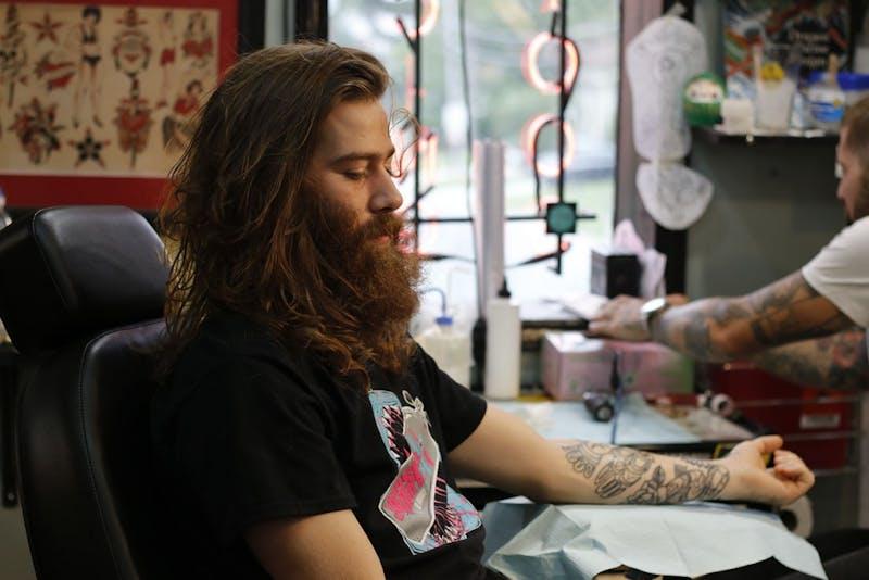 Tattoo artist Mike Wheeler shades a tattoo at Glenn's Tattoo Service