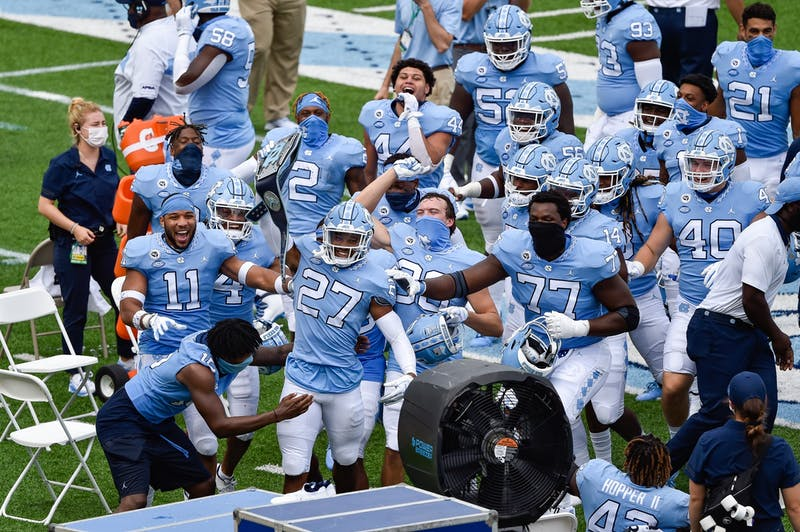 UNC's football team cheers as sophomore defensive back Giovanni Biggers (27) hoists aloft the 'turnover belt' after an interception during a game against Syracuse in Kenan Memorial Stadium on Saturday, Sept. 12, 2020. UNC beat Syracuse 31-6.