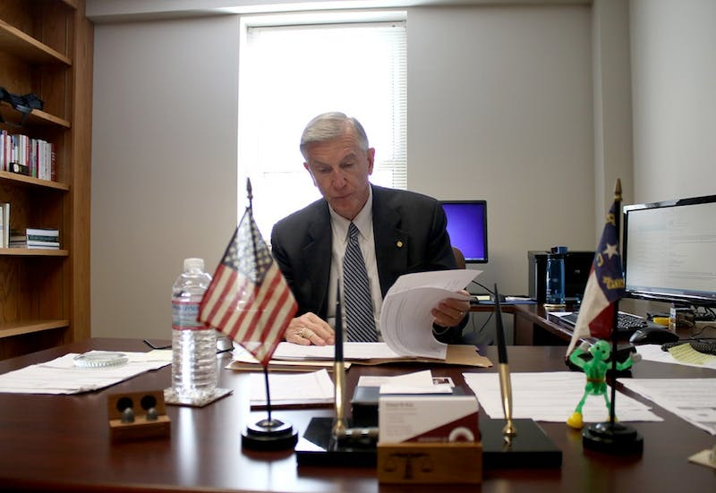 Former UNC-System President, Tom Ross, glances at documents in his office.