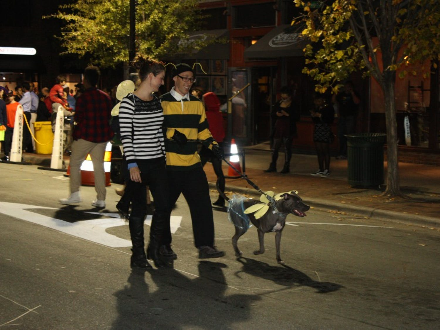 Two individuals walk down Franklin Street with their dog on Halloween night.