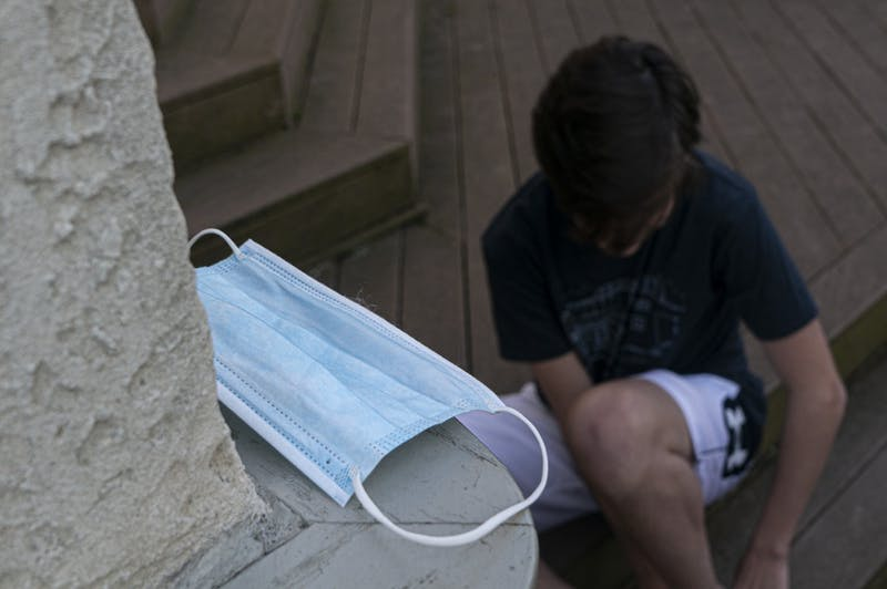 A student puts on his shoes before leaving his house on Wednesday, May 20, 2020. Upon re-opening in the fall, it will be required for students to wear masks when they are in public.