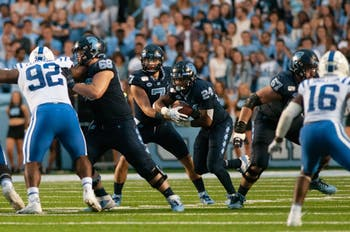 First-year quarterback Sam Howell (7) passes the ball to senior running back Antonio Williams (24) in the homecoming game against Duke on Saturday, Oct. 26, 2019 in Kenan Memorial Stadium.  UNC defeated Duke 20-17 for the first time in three years.