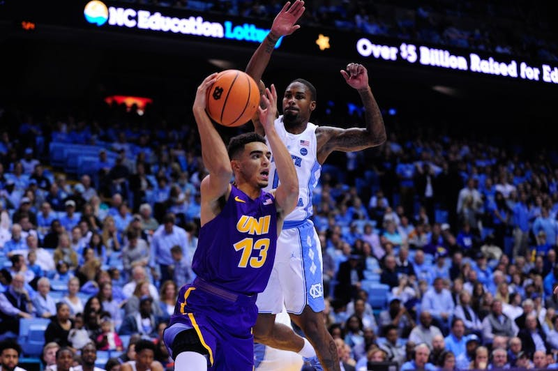Sophomore Seventh Woods goes up for a block behind a UNI player on Friday night.