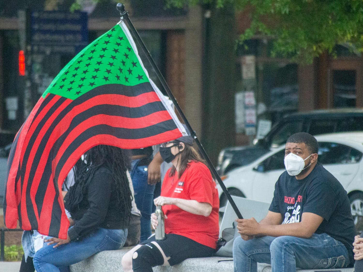 An attendee of a community organized vigil in memory of Daunte Wright and Jaida Peterson holds an African-American flag. The vigil took place in Moore Square Park in downtown Raleigh on Sunday Apr. 18, 2021.