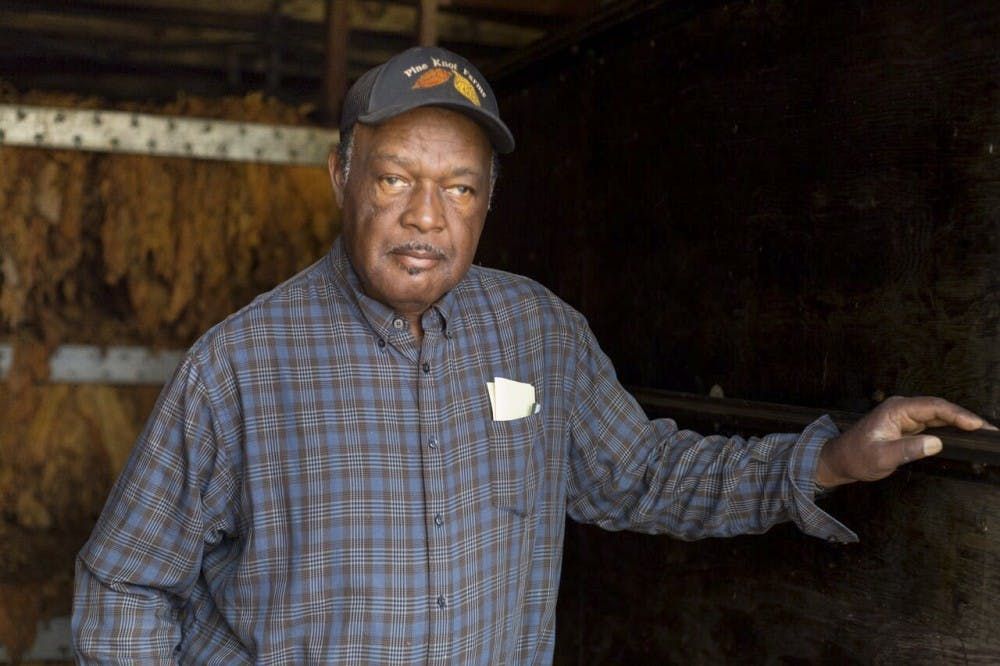 <p>Stanley Hughes poses for a portrait in front of tobacco drying racks at Pine Knot Farms on Monday.</p>