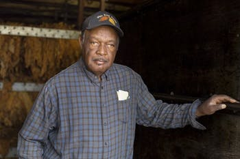 Stanley Hughes poses for a portrait in front of tobacco drying racks at Pine Knot Farms on Monday.