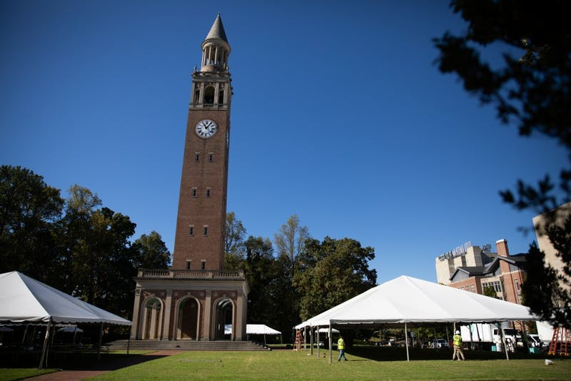 Crews prepare tents on the open area at the foot of the belltower in preparation for football tailgaters in Chapel Hill on Thursday, Oct. 24, 2019.