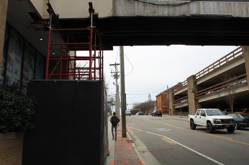 A student walks by scaffolding next to 136 E Rosemary St on March 4, 2020 where a sky bridge is currently being constructed to reach across East Rosemary Street.