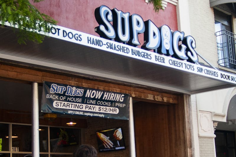 A Now Hiring banner hangs above Supdogs, one of the many off-campus places that frequently hires students, on Tuesday, June 23, 2020.