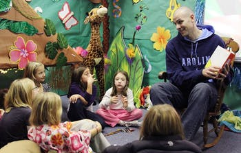 Eric Montross, former UNC basketball player and NBA player, reads to children at Read-a-thon Night at Frank Porter Graham Elementary School on Wednesday night.