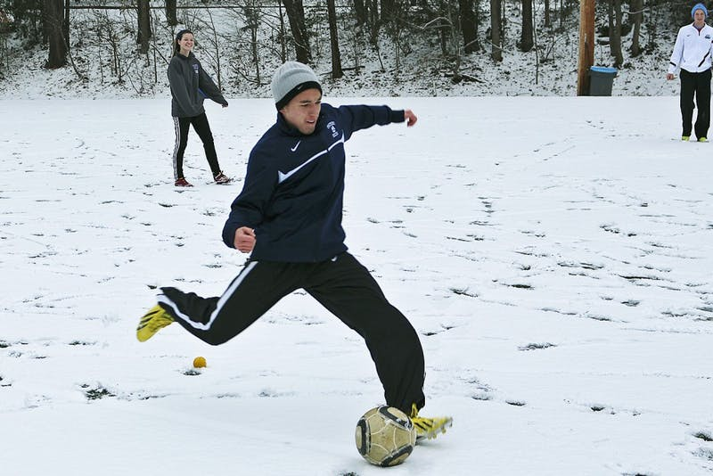 Freshmen Trevor Doane (right) and Megan NcNeill play soccer in the snow on Ehringhaus fields Tuesday. Classes were canceled at 2:30 p.m.