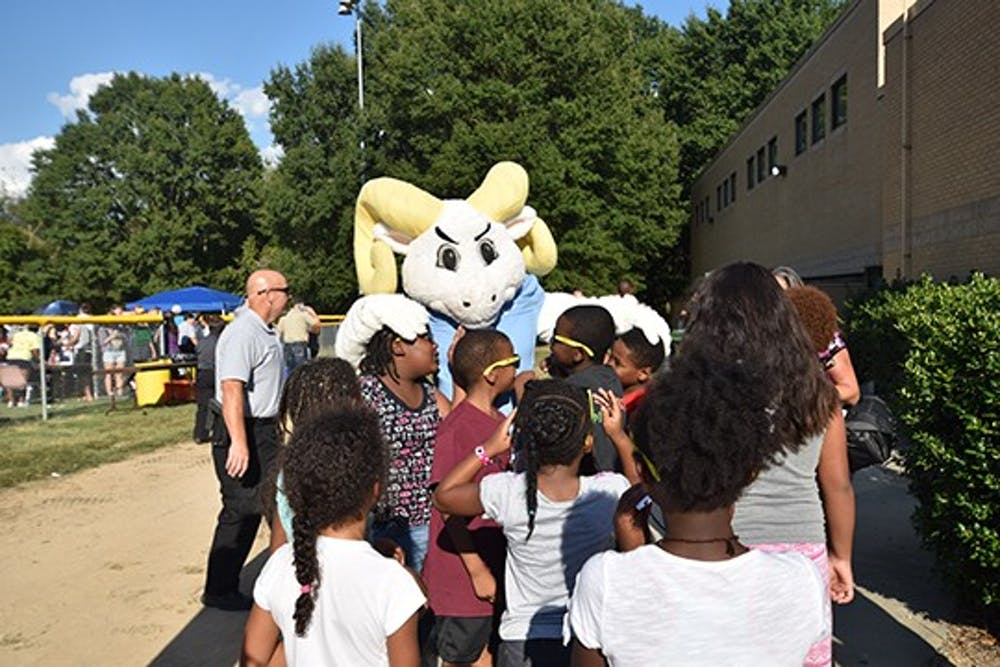 Ramses embraces a group of local children at the good neighbor block party at Hargraves Community Center on Tuesday evening.