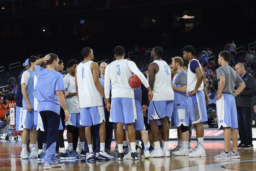 <p>The UNC men's basketball team huddles up at center court.</p>