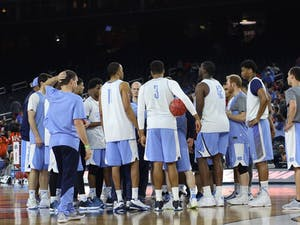 The UNC men's basketball team huddles up at center court.