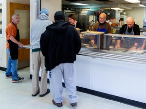 Volunteers serve lunch to diners at the IFC Community Kitchen before the pandemic, when community members shared meals and conversation together in the dining room. Photo courtesy of the Inter-Faith Council.