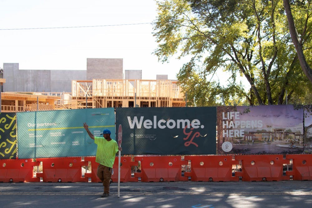 <p>Travis Arnold, 31, of Louisburg, directs traffic around construction at Glen Lennox Apartment Complex on Tuesday, Sept. 24, 2019. Glen Lennox recently announced they will be naming a building in their expansion after Gwendolyn Harrison, the first black woman to attend UNC.&nbsp;</p>