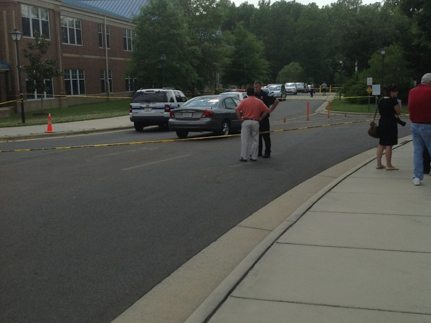 A police officer talks with a parent at Mary Scroggs Elementary School after a shooting on May 25.