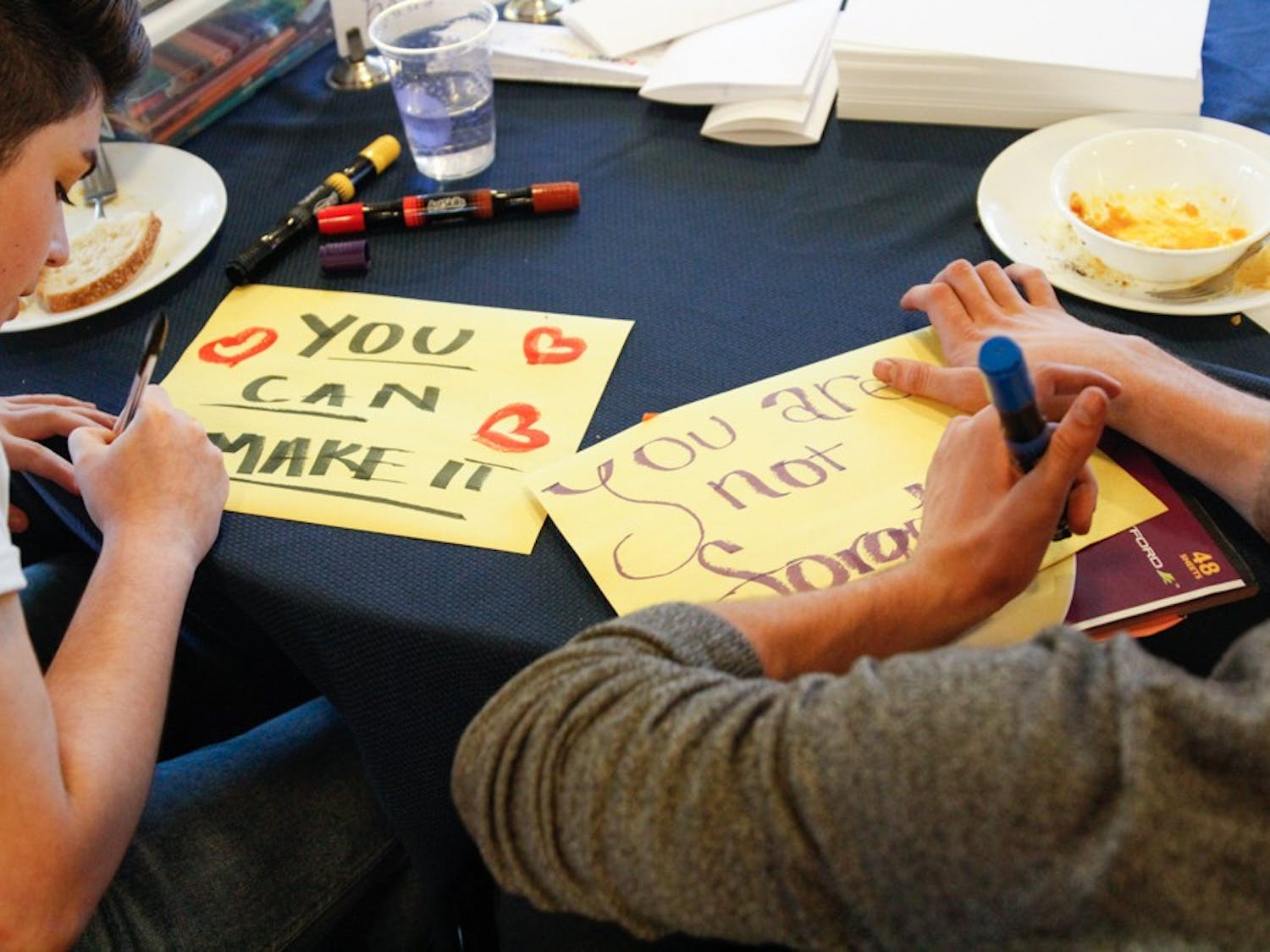 (From left to right) Gaby Taccir, visual designer at R65 labs and Chris Corsi, program assistant at UNC Student Wellness, write letters for Kanautica Zayre-Brown at the Queer Family Gathering dinner at a community building in Carrboro, Tuesday, March 19, 2019. Kanautica is a trans woman incarcerated at a men's prison and who has been in solitary confinement for 17 days. The letters are meant to help Kanautica maintain her mental health during her confinement until she can be moved into a women's facility.