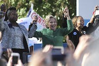 Democratic presidential nominee Hillary Clinton (center) holds hands with Mothers of the Movement members Sybrina Fulton (left), the mother of Trayvon Martin, and Lucy McBath (left), the mother of Jordan Davis. Mothers of the Movement is a group working to end police brutality.