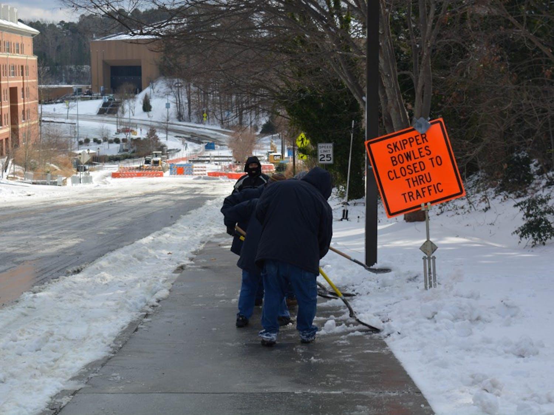 Workers clean the sidewalk on Skipper Bowles Drive.