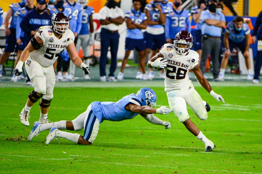 Texas A&M's sophomore running back Isaiah Spiller (28) evades UNC's junior defensive back Trey Morrison during the Capitol One Orange Bowl in Hard Rock Stadium in Miami on Saturday, Jan. 2, 2021.  Texas A&M beat UNC 41-27.