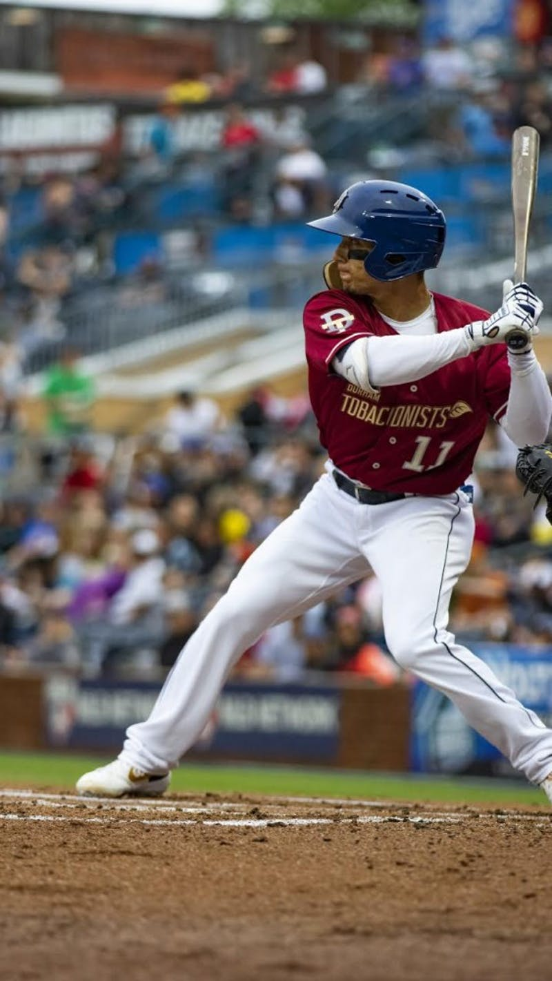Andrew Velazquez taking an at bat for the Durham Bulls in their throwback uniforms honoring the team's original name, the Durham Tobaconists. Photo by Patrick Norwood/Durham Bulls Photographer