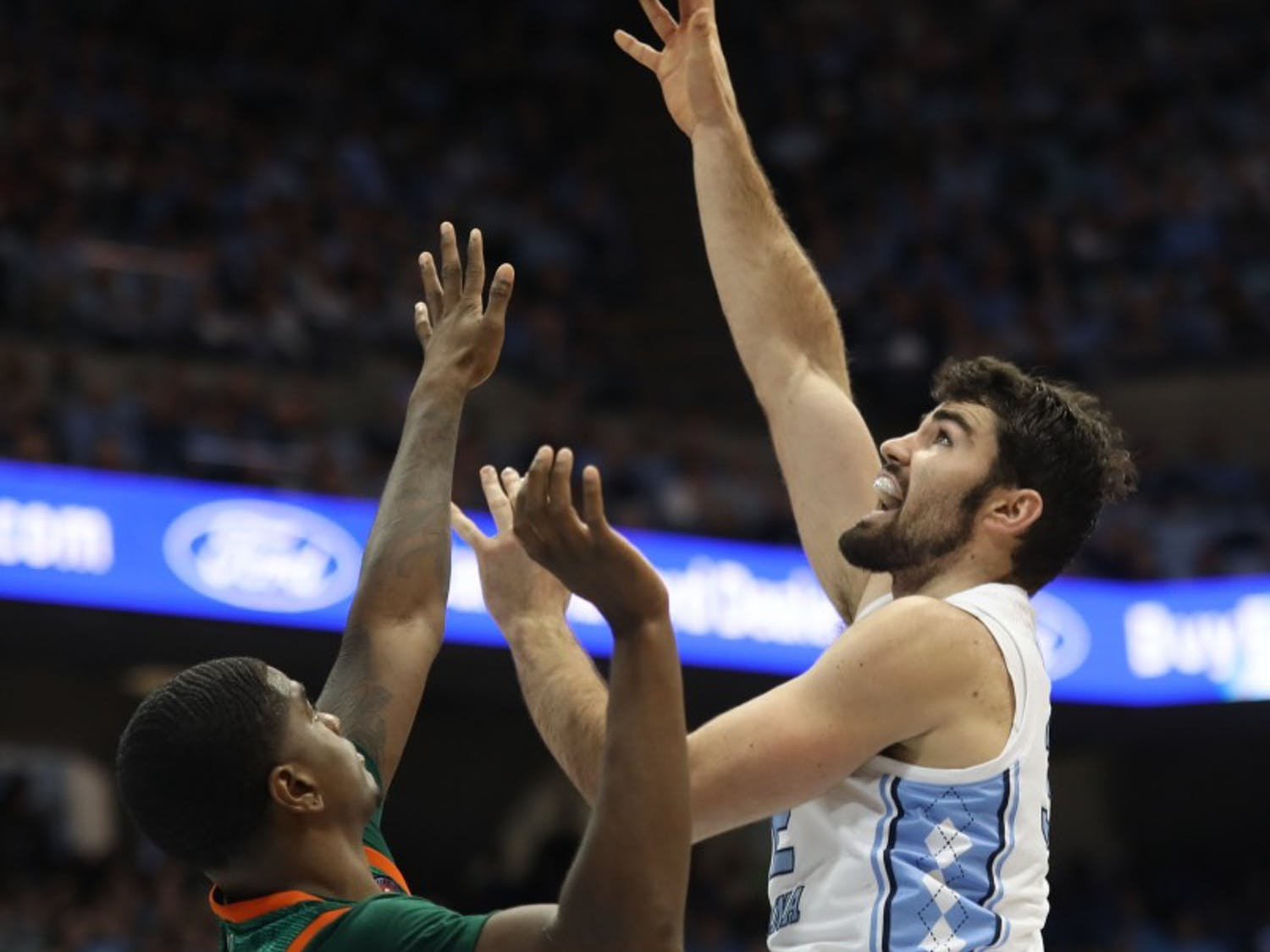 Miami senior guard Anthony Lawrence II (3) attempts to block a shot by UNC senior forward Luke Maye (32) on Saturday, Feb. 9, 2019 in the Smith Center. UNC men's basketball defeated Miami 88-85 in overtime. Maye scored 20 points for the Tar Heels.