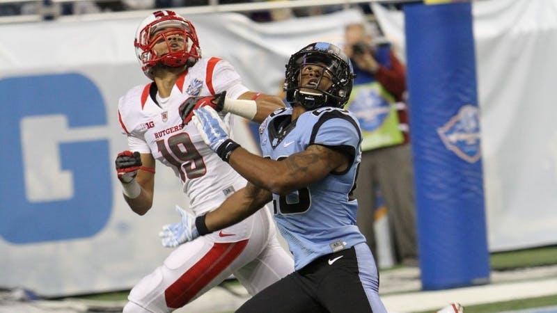 Rutgers senior wide receiver Andrew Turzilli (19) catches a touchdown pass over a Tar Heel defensive back in UNC's 40-21 loss to the Scarlett Knights in the Quick Lane Bowl.