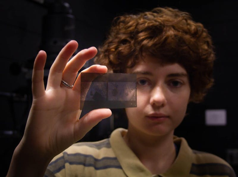 """Sophie Payne, a sophomore English major at UNC, holds a lithofilm negative which she will use to get higher contrast in her final enlargened print in an advanced Darkroom Photography class on Thursday, Oct. 10, 2019. """"I always push my film which means that my film has more contrast. I like blacks and whites, I don't like as many greys. So, a lot of my images are intense,"""" Payne said."""