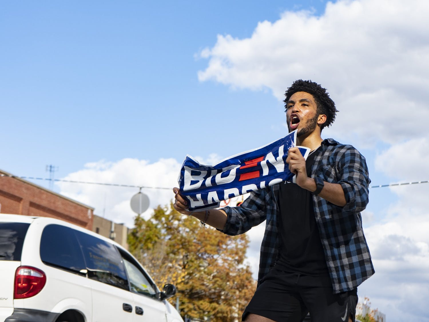 Eliam Mussie waves his Biden Harris sign at the cars on Franklin Street to get them to honk their horns and celebrate the announcement of Former Vice President Joe Biden's election to the presidency on Saturday, Nov. 7, 2020.