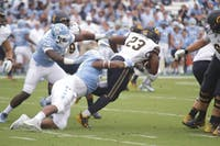 Cal running back Vic Enwere drags UNC defenders on Saturday.