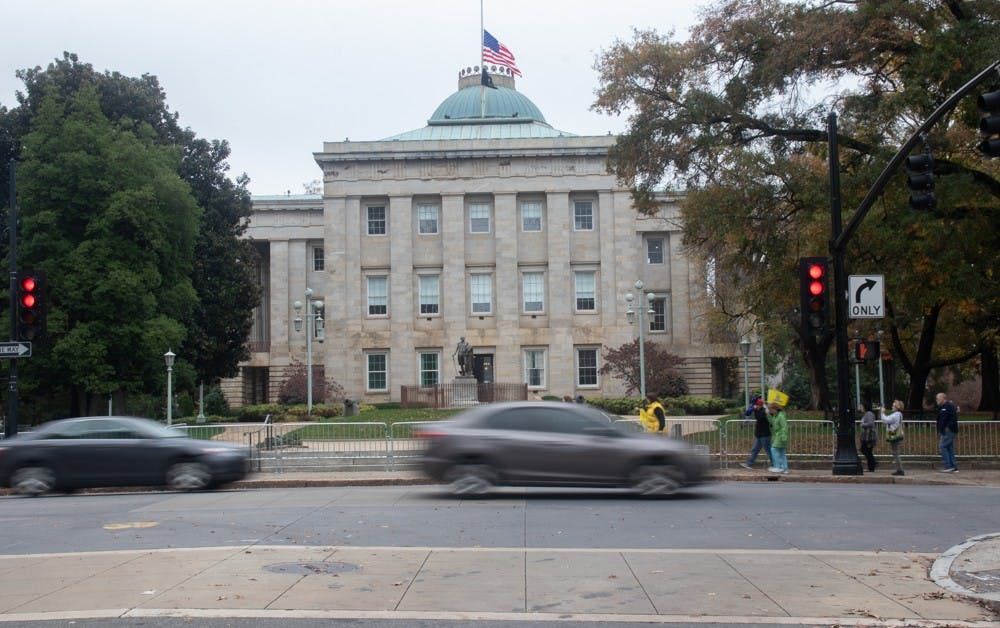 <p>Cars pass by the North Carolina State Capitol building on Friday, Nov. 13, 2020. In the 2020 election, all of the incumbents in the council of state races won re-election or are leading over their opponent.</p>