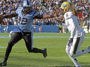 Marquise Williams (12) stiff arms a Pittsburgh defender.