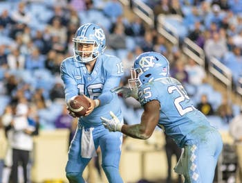 Quarterback Manny Miles (16) hands the ball to running back Javonte Williams (25) during the home football game vs. Western Carolina on Saturday, Nov. 17 2018.