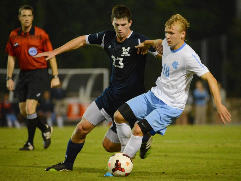 UNC midfielder Verneri Valimaa (18) makes a cut as UNC Wilmington midfielder Seo-In Kim (23) defends.