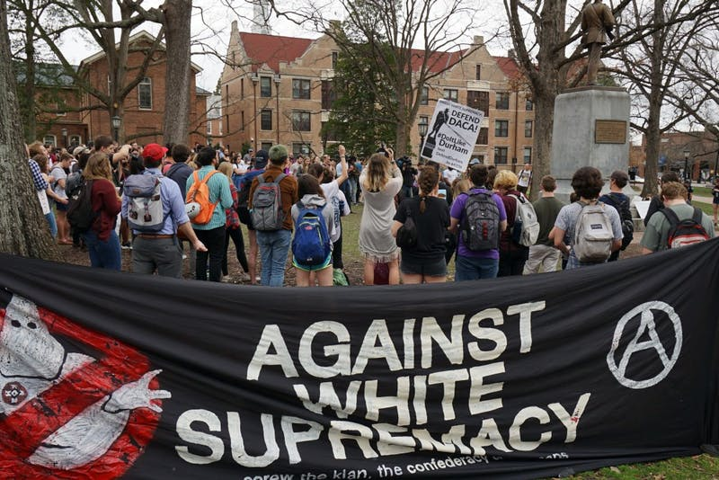 Students and faculty held signs and banners against Silent Sam, DACA repeals and Silent Sam at a campus rally on Wednesday.