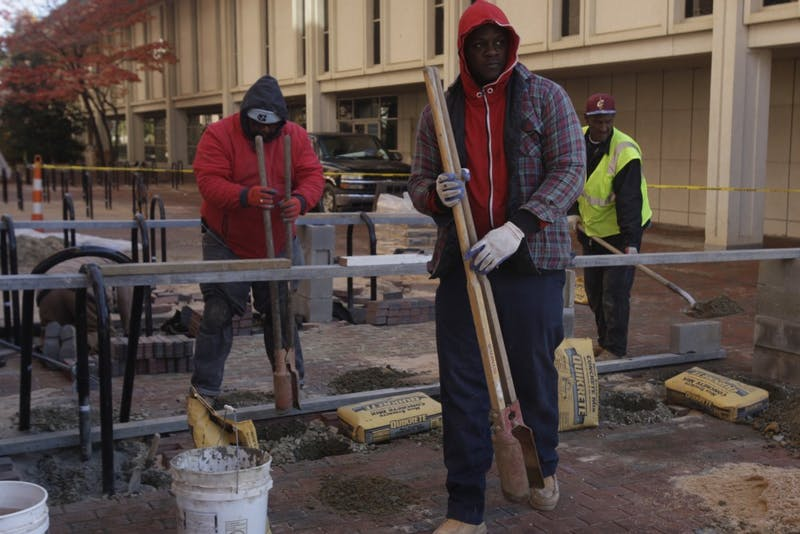 """We're an old university, and we have hundreds of millions of dollars in deferred maintenance,"" said Chancellor Carol Folt at the November BOT meeting. ""You hit a point when old buildings get old. We're trying to deal with that. We can't rely fully on the state."" President of the Graduate and Professional School Federation and Student Body President said the University introduced the new fee controversially, undermining student feedback which typically guides the early stages of fee creation. Curtis Love, 45, from Alamance County, Richard Smith, 42, from Greensboro, and  Carnell Bass, 55, from Durham on Nov 28, 2018 working on brick construction in between Davis library and the student union."