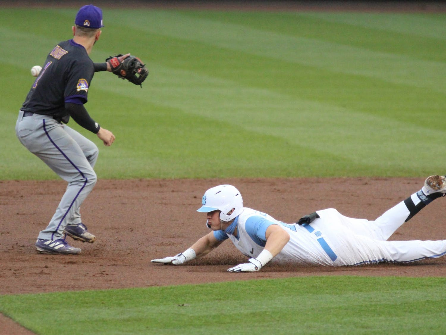 UNC junior right-handed pitcher Michael Oh (1) attempts to slide into first base before getting tagged out by ECU infielder Connor Norby during the Tar Heels' game against East Carolina University at Boshamer Stadium on March 23, 2021. The Tar Heels defeated the Pirates 8-1.