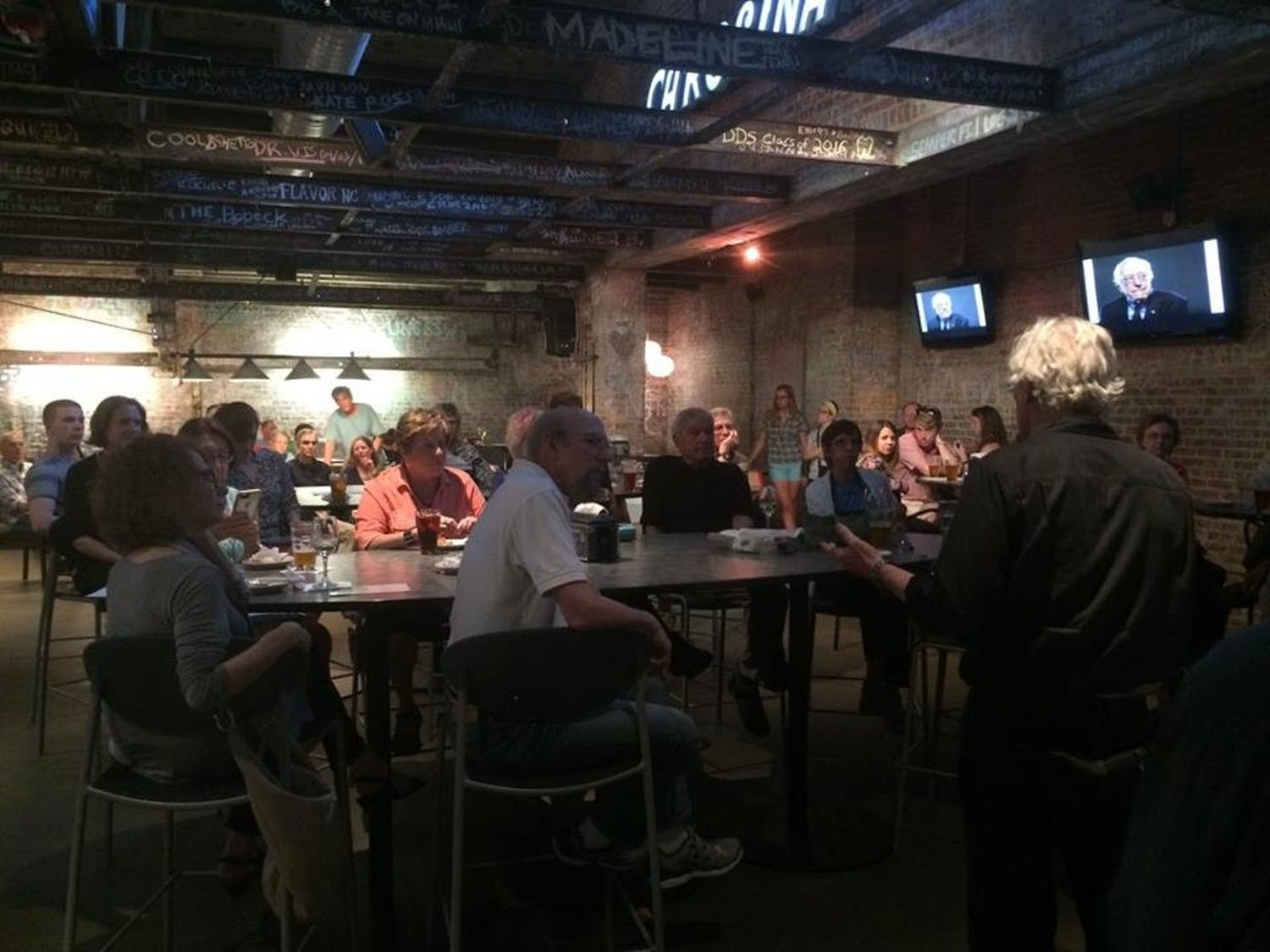 Lecture being given at Humanities Happy Hour at Top of the Hill's Back Bar