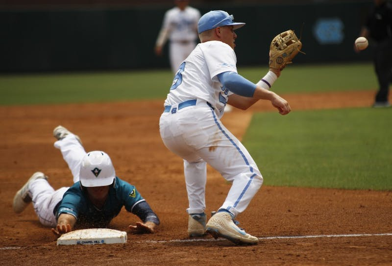 UNC baseball junior and short stop, Ike Freeman, prepares to catch the ball while a UNCW player sides into third base during the Tar Heel's first game in the regional championship versus UNCW on Friday May 31, 2019. UNC won 7-6.