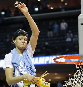 North Carolina wing Justin Jackson (44) holds up a piece of the net after UNC's win over Kentucky in the NCAA Elite Eight game in Memphis on Sunday.