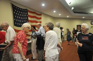 Members of the Carolina Meadows community gather around a flag and uniforms on display during their Memorial Day event.