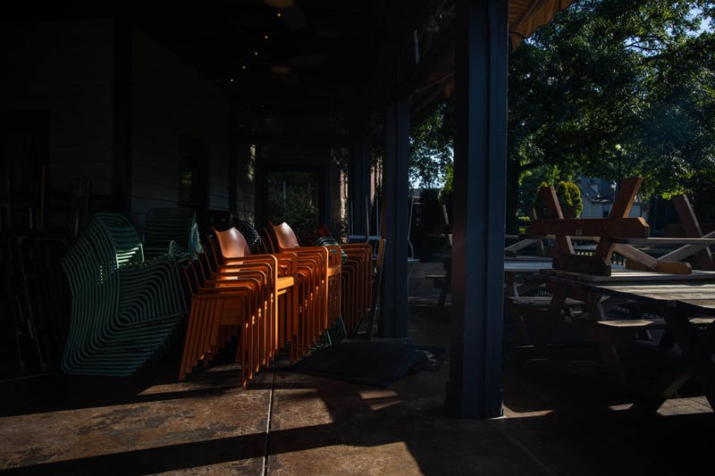 Stacked chairs and picnic tables sit unused in the outdoor eating area of The Pickle Peach in Davidson, NC on Thursday, May 14, 2020. Restaurants like this and many other businesses across the state are losing business due to the COVID-19 pandemic.