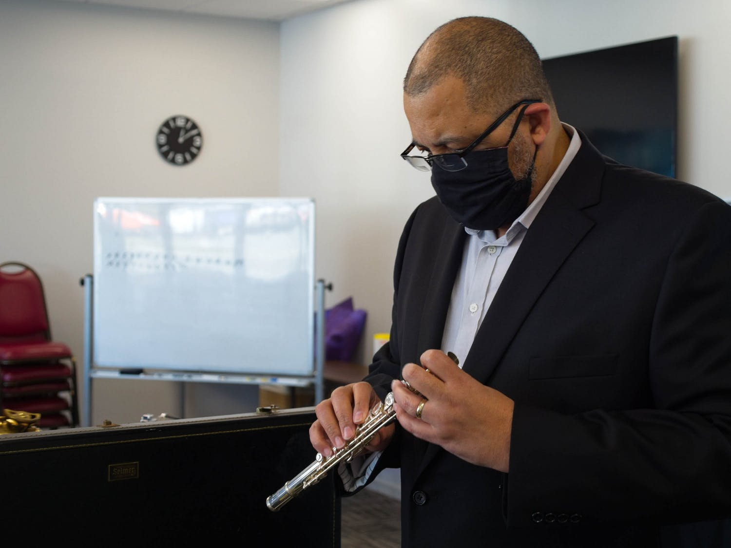 Ralph Barrett, an Assistant Professor of NC Central University's Music Department, examines a donated flute in the YouthWorx conference room on Wednesday, Dec. 9, 2020. Barrett is a member of Musical Empowerment's Board of Directors.