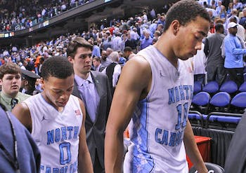 Brice Johnson and Nate Britt hang their heads as they exit the court after UNC lost to Pittsburgh 80-75 in the ACC Tournament at the Greensboro Coliseum.