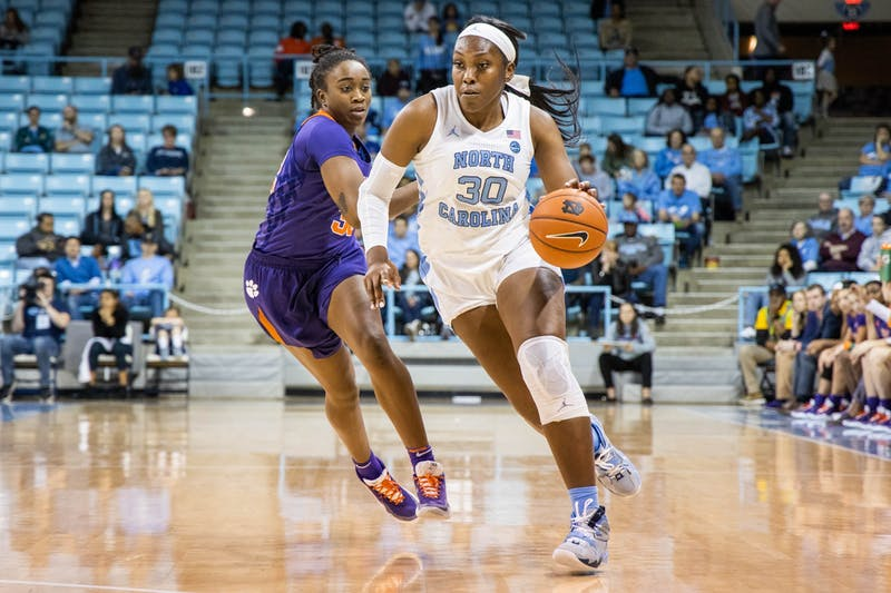 UNC junior center Janelle Bailey (30) dribbles past Clemson University senior guard Chyna Cotton (32). The Tar Heels beat the Tigers 86-72 on Sunday, Feb. 2, 2020 in Carmichael Arena.