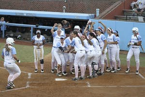 The team celebrates after Tracy Chandless, a junior from Canyon Country, California, hit a home run during a preseason game against North Carolina Central University on October 8, 2014.