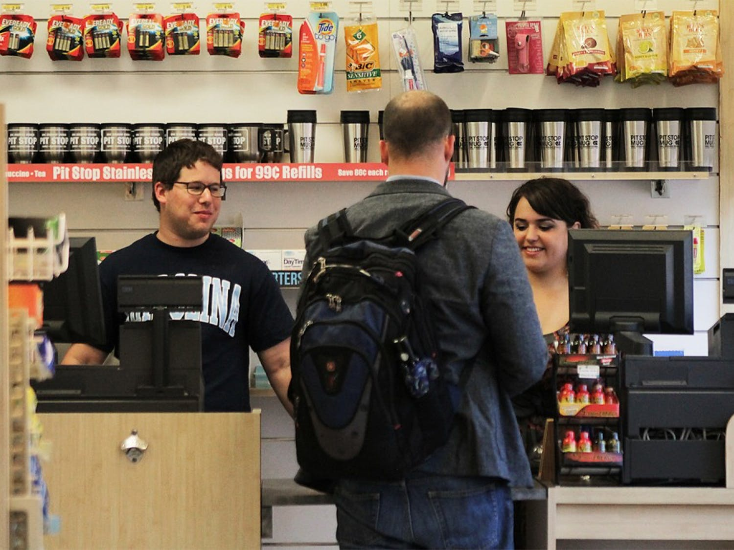 David Deans, from Rocky Mount, N.C. (left) and Katie Coletta (right), senior at English program, from Cary, N.C. are helping Michael Knight, a Ph.D candidate at the Department of Religious Studies check out snacks he buys Tuesday at the Pit Stop.