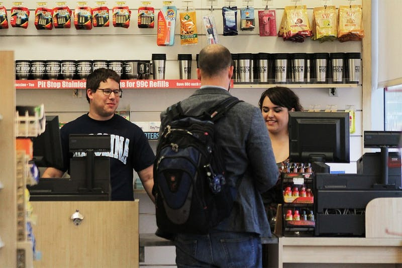 David Deans (left) and Katie Coletta help Michael Knight purchase snacks at the Pit Stop on Tuesday after the store reopened.